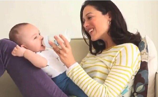Cho bé bú bình ở tư thế ngồi tự lên đùi