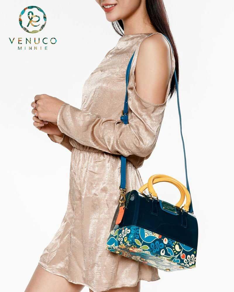 Kết hợp chiếc túi da mềm với họa tiết hoa màu sắc tạo điểm nhấn cho trang phục nhung đơn sắc