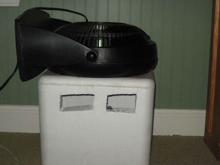 Cho một túi đá vào thùng xốp, khoét 2 lỗ thông và dùng quạt úp xuống như hình, hơi mát từ đá sẽ bốc lên làm mát căn phòng