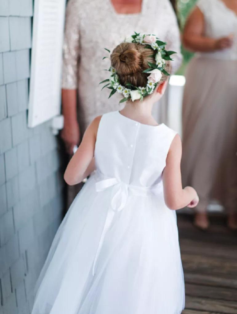 Hình ảnh bé gái tóc dài búi cao và đội chiếc vòng hoa giống với loài hoa mà cô dâu đang cầm sẽ vô cùng tuyệt vời. Đây là kiểu tóc dễ làm và giúp các bé trở nên gọn gàng, tròn trịa hơn!