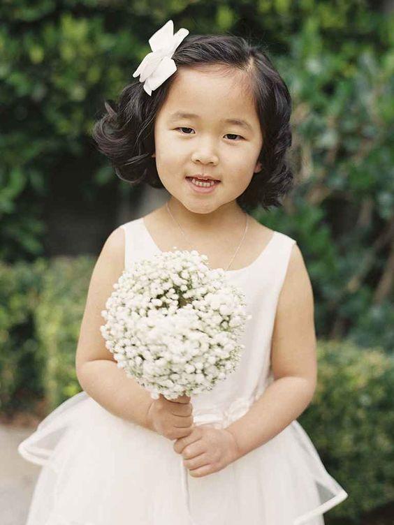 Thay vì đội vòng hoa lên đầu, bé có thể được cài một chiếc nơ to bản lên mái tóc. Trông dễ thương quá, phải không nào?