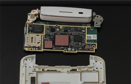 Cận cảnh mạch chính với rất nhiều chip xử lý, một số được phủ lớp bảo vệ, một số có thể thấy rõ như Qualcomm MDM8215M&