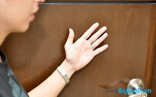 Cảm nhận sức nóng bên ngoài bằng cách áp mu bàn tay vào cửa